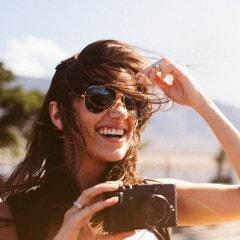 Una ragazza bruna con gli occhiali e i capelli al vento.