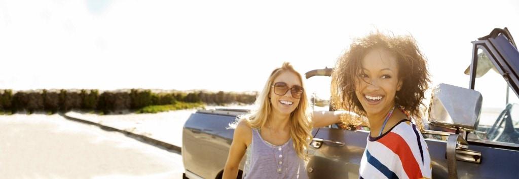 Due donne sorridenti, una con capelli lisci, asciutti, l'altra con capelli ricci, asciutti, vicino a un'auto.