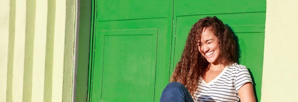 Una donna con capelli ricci sani ride e si diverte, seduta sul pavimento.