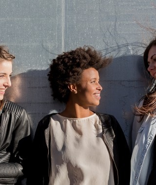 Three women leaning against a wall with beautiful hair to illustrate the page with the Silk product line.