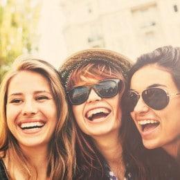 Tre amiche con capelli crespi e ondulati si scattano un selfie